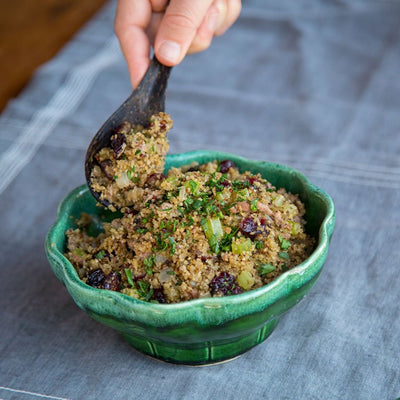Spooning mushroom and KAMUT grains with cranberries and green onion into a ceramic serving bowl
