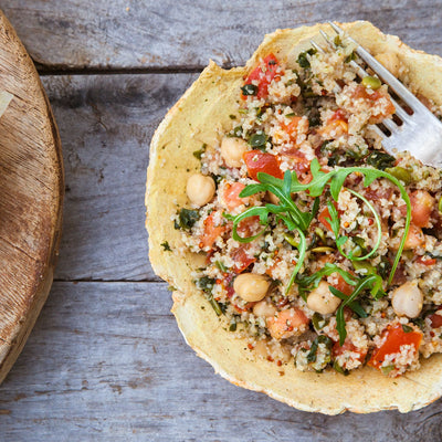 Grains and KAMUT combined with tomatoes, garbanzo beans, and salmon in a tortilla bowl
