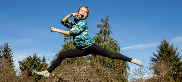 A pre-teen in black leggings and puffy jacket leaps through the air with a Patagonia Provisions Fruit + Almond Bar