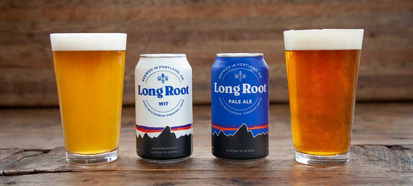 Two filled pint glasses sit next to their cans of Patagonia Provisions Long Root Ale and Long Root Wit beer, on a wooden table