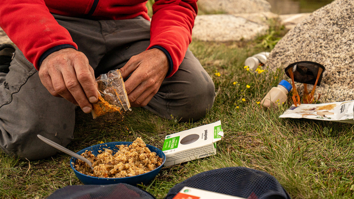 Camper kneeling in grass with close up shot of hands opening spices to add to bowl of grains