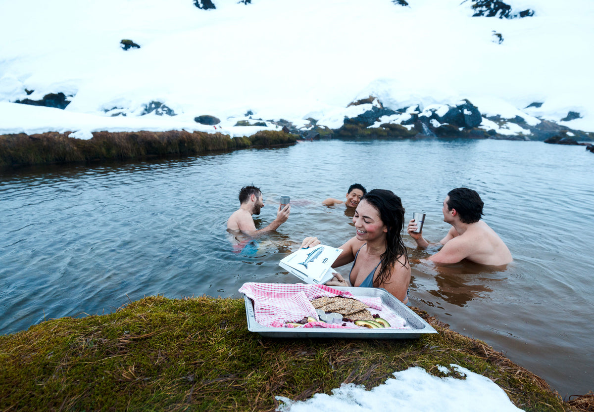 Swimmers in a natural pool surrounded by snowy banks pause for snacks of crackers, avocado, and Patagonia Provisions wild smoked salmon