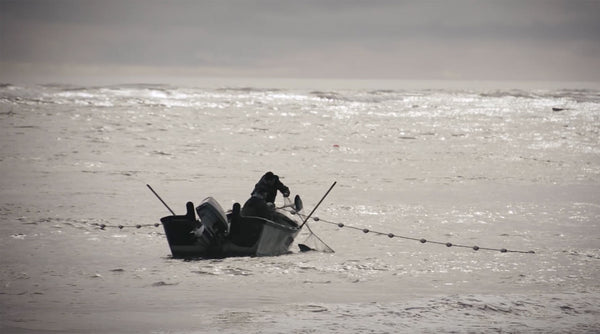 Fishermen on a small boat raise a net strung with small buoys