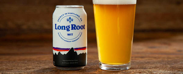 A can of Patagonia Provisions Long Root Wit rests next to a full pint glass on a wooden table