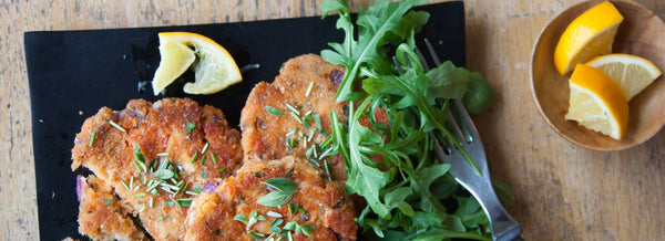 Wild Salmon Cakes on a black plate with arugula, old fork next to a bowl of lemon wedges