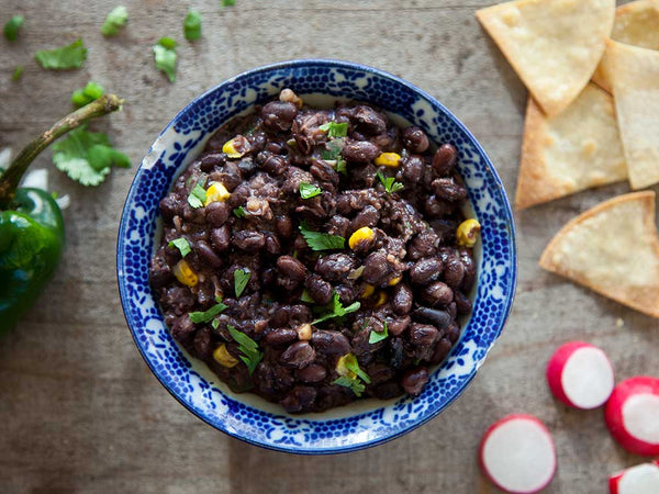 Blue bowl filled with black bean dip and sprinkled with cilantro