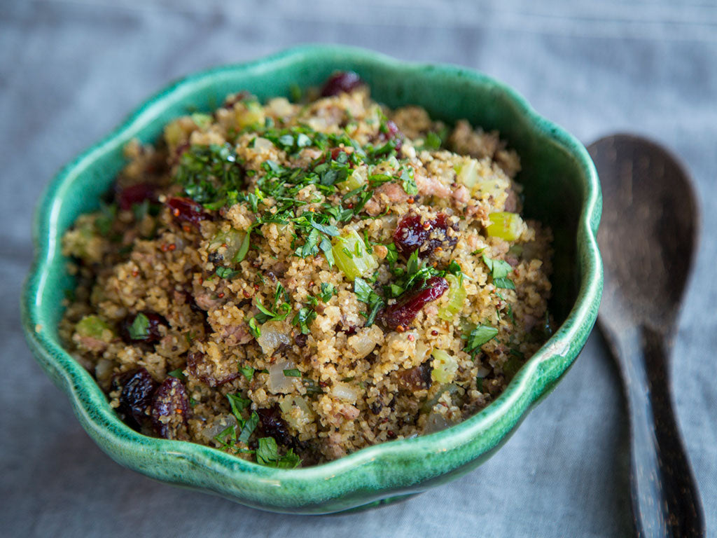 bowl of savory grains stuffing with spoon