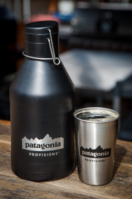Black MiiR® double walled Growler and stainless Pint Cup with Patagonia logo on wooden background