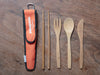 All bamboo utensils with orange to-go sleeve on wood background.