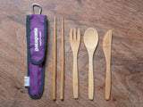 All bamboo utensils with purple to-go sleeve on wood background.