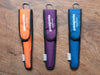 Orange, Purple, and Blue to go sleeve for bamboo utensil set on wood background.