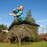 A child wearing a blue patterned puffy jacket and black leggings leaps through the air while biting a Patagonia Provisions Organic Fruit and Almond bar