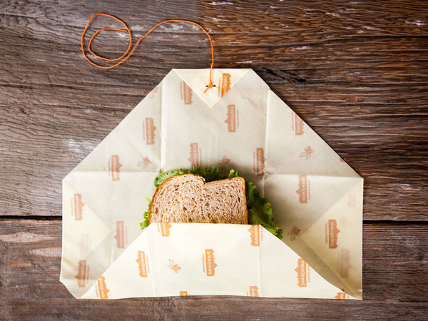 Bees Wrap® folding over a sandwich on wood background.