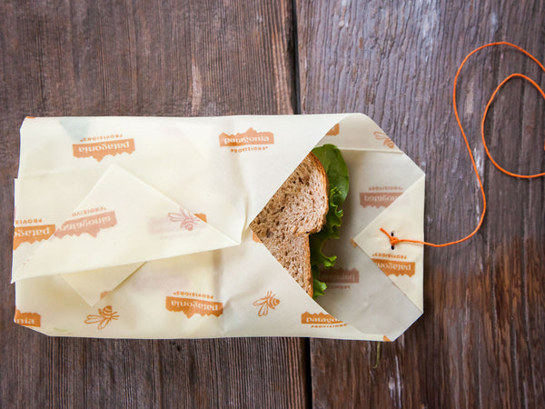 Bees Wrap® almost fully enveloping a sandwich on wood background.