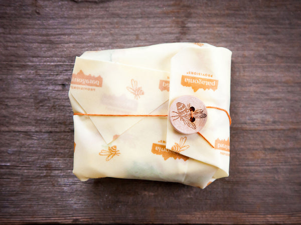 Fully wrapped sandwich in Bees Wrap® on wood background.