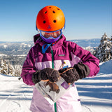 A skier on the slopes, wearing an orange helmet and purple jacket, opens a packet of Patagonia Provisions Original Buffalo Jerky with mittened hands