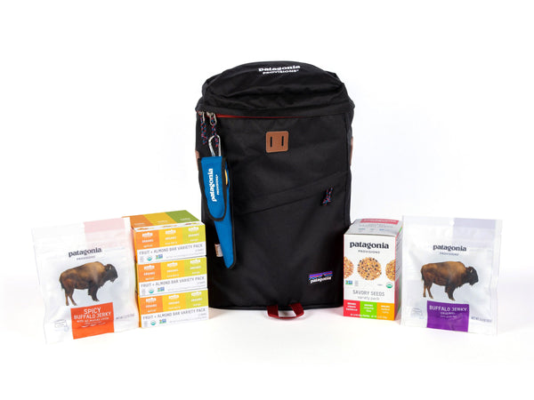 Black Patagonia backpack with organic energy bars, savory seeds, buffalo jerky, and a bamboo utensil set