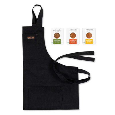 Black Patagonia apron on white surface next to three Patagonia Provisions Spice Packets