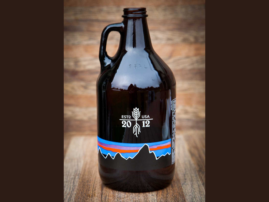 64-oz Glass Long Root Ale Growler on wood background, backside view.