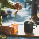 Close shot of hands scooping Patagonia Provisions Organic Moloka'i Honey from the jar with a small wooden spoon, to drizzle into a steaming ceramic cup