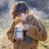 Youth outdoors on cold morning, wearing fleece jacket, scooping hot food out of Patagonia Provisions Klean Kanteen TKCanister
