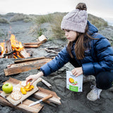 A child wearing cozy winter clothing crouches at the top of sand dunes beside a small bonfire and places Patagonia Provisions Organic Chile Mango slices on a cuting board beside crackers, apple, and cheese