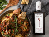 Bottle of Bona Furtuna Biancolilla Centinara - Single Varietal, Organic Extra Virgin Olive Oil on cloth napkin next to polenta dish with sauce and rosemary