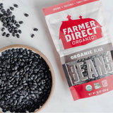 Bowl of dried Farmer Direct Organic Black Beans on white table, next to package