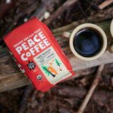 Bag of Peace Coffee Organic Tree Hugger Signature Blend out doors on board, next to two mugs of coffee