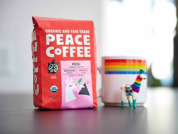 Peace Coffee Organic Peru Single Origin coffee bag next to mug and toy alpaca in rainbow stripes