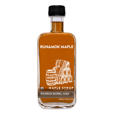 Glass bottle front of Runamok Maple Bourbon Barrel-Aged Maple Syrup