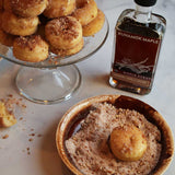 Glass bottle of Runamok Maple Cinnamon Vanilla Maple Syrup beside a plate of doughnuts and bowl of cinnamon topping