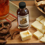 60ml bottle of Runamok Maple Bourbon Barrel-Aged Maple Syrup on table beside cheese squares and pretzels