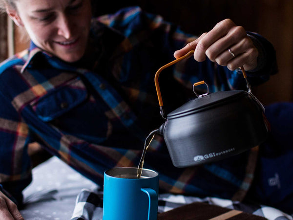 Numi Organic Aged Earl Grey Tea lifestyle shot of man pouring tea from black kettle into blue mug
