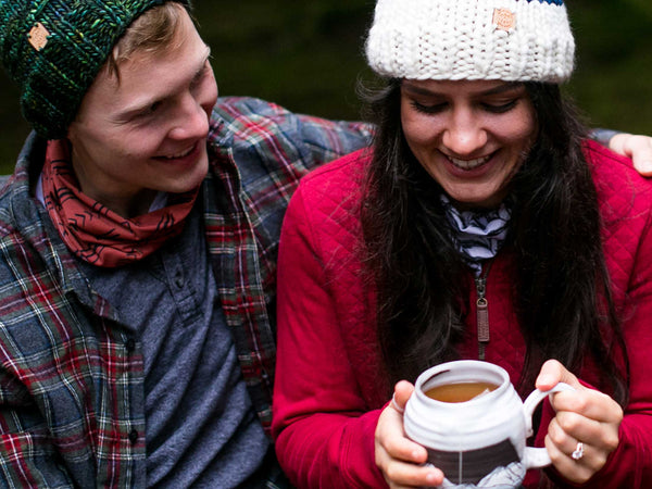 Numi Organic Rooibos Chai Tea Lifestyle shot of smiling couple wearing warm outdoor clothing with woman holding ceramic mug of tea