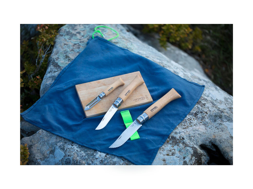 Outdoor shot of Opinel Nomad Knife and peeler set on cutting board and cleaning cloth atop a rock