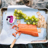 Patagonia Provisions Pacific Northwest Wild Sockeye Salmon on a metal tray with crackers, goat cheese and grapes