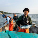 Two fishermen on a boat, one holding a wild salmon for Patagonia Provisions Wild Sockeye Salmon