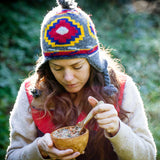 Woman in knitted hat and cold weather clothing stands outside scooping Patagonia Provisions Organic Tsampa Soup, Garden Veggie from a wooden bowl with a wooden spoon