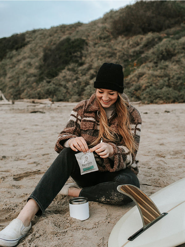 Smiling girl opening pouch of Steeped Coffee Dawn Patrol before surfing Ventura County, CA