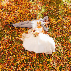 bride and groom laying on ground with vibrant colored fall leaves on ground surrounding them