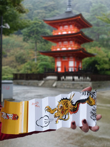 hands holding a dragon artist papes in front a japanese monument