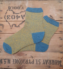 A pair of teal and gold stripy hand knitted socks in Regia Premium Silk
