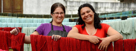 Two women standing behind hand dyed yarn drying