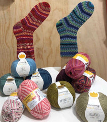 Selection of Regia Sock Yarn in front of 2 hand knitted socks, one red and one blue