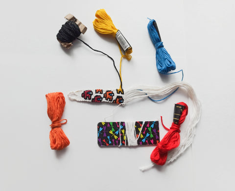 Colourful stranded cotton embroidery floss being tied into a friendship bracelet
