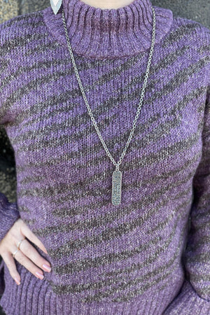 Turtle Neck sweater with angled zebra striped jacquard print on an eggplant background with ribbed neck, cuffs and hem.