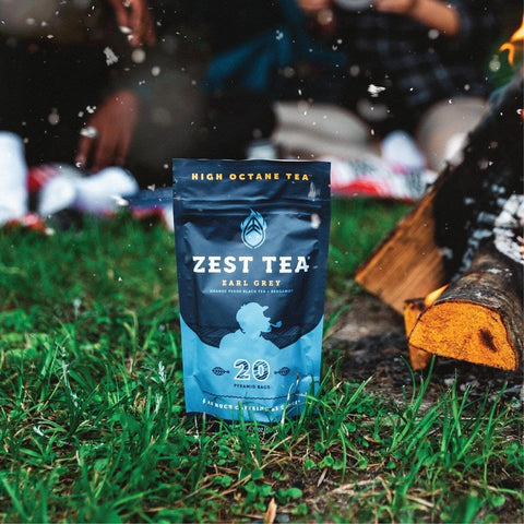 Pouch of Zest Tea Earl Grey standing up on grass at a camp site, with some snow flakes in the air.