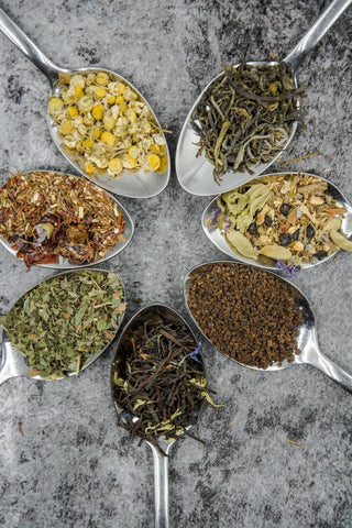 Colorful display of 7 spoons, each containing various types of tea blends