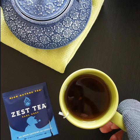 Cup of tea with tea bag still inside, and a Zest Tea Earl Grey opened wrapper displayed next to it.